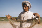 Iraq, man holding twine looped around arms