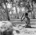 India, woman pounding coconut husk for making coir in Kochi
