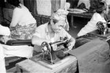 Indonesia, man using sewing machine to sew textiles