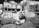 India, vendor sitting with produce at Mahatma Jyotiba Phule (or Crawford) Market in Mumbai