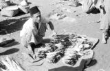 Indonesia, man selling dried fish at market on Sumbawa Island