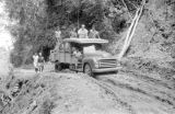 Indonesia, Harrison Forman's escorts driving truck on rutted road to Ruteng