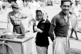 Indonesia, woman eating food sold by vendor in Banjarmasin