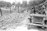 Vietnam, French soldiers driving jeep past bomb crater during First Indochina War