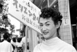Japan, female impersonator carrying sign advertising show in Tokyo
