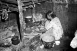 Indonesia, woman cooking inside home on Sumbawa Island
