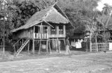 Indonesia, man walking past thatched roof stilt house in Makassar