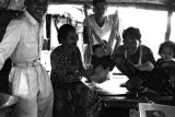 Indonesia, family on boat in Banjarmasin with baby hanging in sling