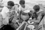 Indonesia, crew eating meal on boat sailing from Bima to Komodo Island