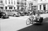 Singapore, men riding bicycle with side car on street