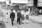 Malaysia, men walking through village wearing fezes