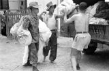 Laos, soldiers loading parachutes onto truck at camp in Xiangkhoang