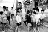 Laos, local children surrounding soldiers at Xiangkhoang