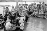 Indonesia, people crowding boats along rocky shore