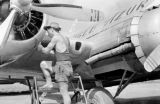 Vietnam, mechanic making repairs to airplane during First Indochina War