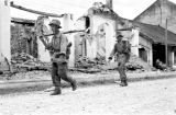 Laos, soldiers walking past burned out buildings in Xiangkhoang