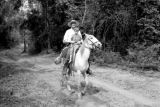 Vietnam, Western man and boy riding horseback on dirt road