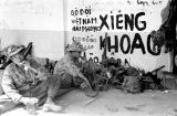 Laos, soldiers resting along graffiti on building wall in Xiangkhoang