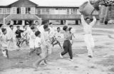 Malaysia, children chasing man with basket at celebration