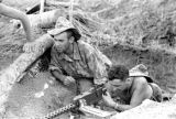 Laos, soldiers aiming machine gun from foxhole in Xiangkhoang