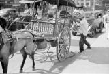 Philippines, men with horse-drawn carriage on street in Manila