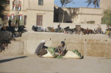 Baquba (Iraq), two men with bags of green vegetables seated near wall