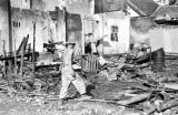 Laos, soldier walking through debris of burned out building in Xiangkhoang