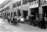 Macau, street scene with pedicabs and sign-covered shops