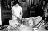 Macau, woman cutting wood at Kwong Hing Tai Firecracker factory