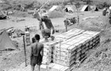 Laos, soldier hammering post around supply crates in Xiangkhoang