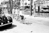 Vietnam, people riding bicycles past car in Ho Chi Minh City street