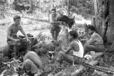 Malaysia, soldiers cooking meal and resting in jungle forest