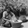 India, woman grinding with stone mortar and pestle in Chennai