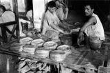 Pakistan, man and boys making bread in Peshāwar
