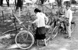 Laos, men watching woman with bicycle near barbed wire fence