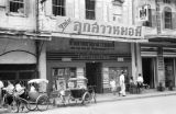 Thailand, pedicabs and pedestrians in front of photographic studio in Bangkok