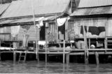 Thailand, woman drying laundry outside river house in Bangkok