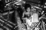 Malaysia, Semang woman sitting next to fire in hut