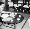 Taiwan, waitress sitting on tatami mats cooking at restaurant in Taipei