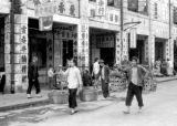 Macau, pedestrians carrying baskets on yokes past shops