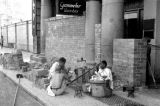 Singapore, men resting from barricading store front with bricks