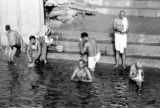 India, men bathing and praying at ghat along Ganges River in Varanasi