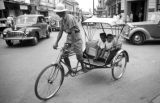 Thailand, two children riding in pedicab in Bangkok street