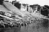 India, men washing fabric at ghat along Ganges River in Varanasi
