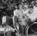 India, man sitting on bicycle with bundle of bracelets in Hyderabad