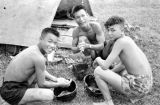 Laos, soldiers washing after eating from helmets in Xiangkhoang