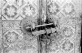 Nepal, metal lock attached to door with flower patterns