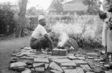 Indonesia, man crouching at burning brazier near pile of grass in Jakarta