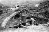 Laos, soldier aiming gun from foxhole in Xiangkhoang