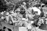 Laos, soldiers riding in truck loaded with crates at Xiangkhoang